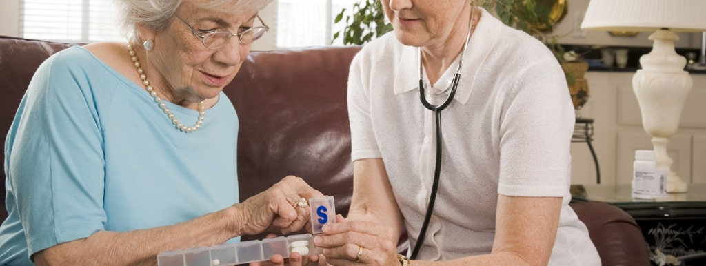 A carer helping a lady with her medication