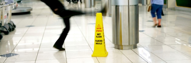 A picture of a man slipping on a wet floor next to wet floor sign