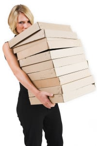 Picture od a woman carrying a stack of boxes