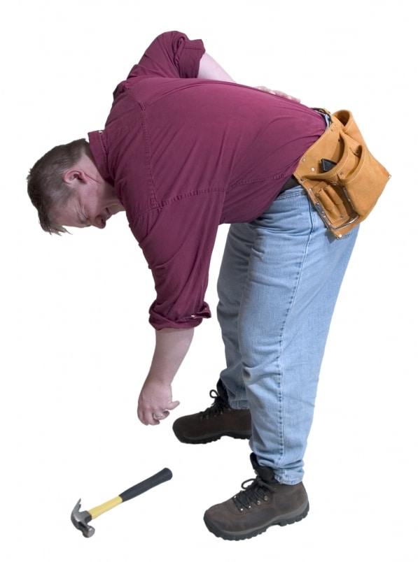 A man bending down to pick up a hammer incorrectly